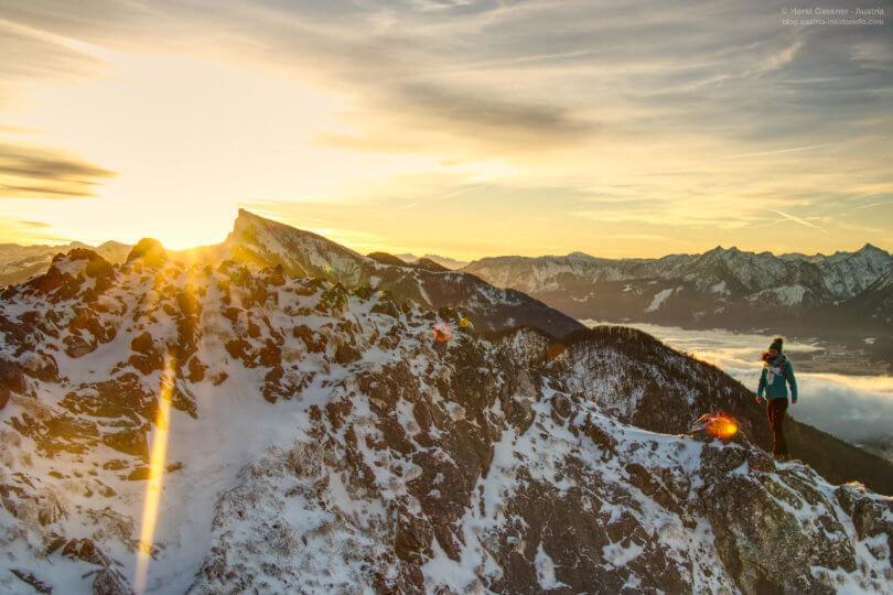 Sonnenaufgang über den Bergen mit junger Frau